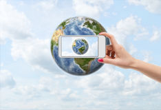 Female hand with smartphone taking photograph of Earth Stock Photo