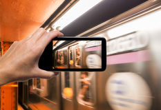 Female hand with smartphone taking a picture of New York subway. Train. Tourism concept Royalty Free Stock Images