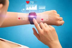 Cardio and smartwatch. Female hand with smartwatch and health application icons nearby Royalty Free Stock Photos