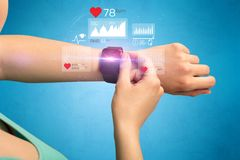 Cardio and smartwatch. Female hand with smartwatch and health application icons nearby Royalty Free Stock Image