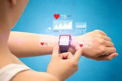 Cardio and smartwatch. Female hand with smartwatch and health application icons nearby Stock Photo