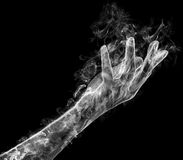 Female hand from a smoke. Graceful female hand from a smoke on a black background. Mysterious and magic art Royalty Free Stock Photo