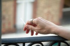 Female hand with a smoking cigarette stuck out the window so as not to smoke in the apartment, against the background of the royalty free stock images