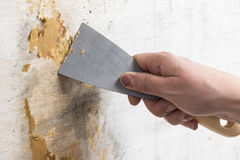 Female hand with a spatula protects the wall Royalty Free Stock Photography