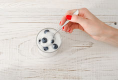 Female hand with a spoon yogurt with blueberries on white wooden table Stock Photo