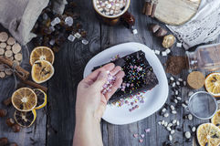 Female hand sprinkles sugar hearts piece of Sachertorte Stock Photo