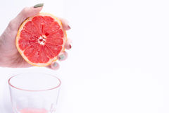 Female hand squeezes of a grapefruit, grapefruit juice on white background. Female hand squeezes of grapefruit, grapefruit juice on white background Royalty Free Stock Photo