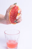 Female hand squeezes of a grapefruit, grapefruit juice on white background. Female hand squeezes of grapefruit, grapefruit juice on white background Stock Images