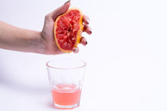 Female hand squeezes of a grapefruit, grapefruit juice on white background. Female hand squeezes of grapefruit, grapefruit juice on white background Royalty Free Stock Photography