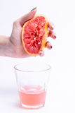Female hand squeezes of a grapefruit, grapefruit juice on white background. Female hand squeezes of grapefruit, grapefruit juice on white background Royalty Free Stock Photos