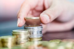 Female hand stack euro coins to shown concept of growing business and wealthy. Saving money concept Stock Photos