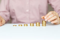 Female hand stacking gold coins into increasing columns Stock Image