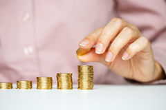 Female hand stacking gold coins into increasing columns Royalty Free Stock Images