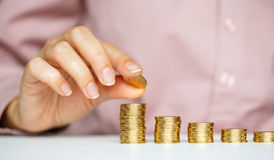 Female hand stacking gold coins into increasing columns Royalty Free Stock Image