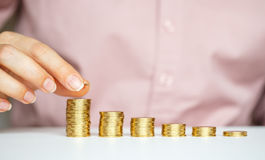 Female hand stacking gold coins into increasing columns Stock Photos
