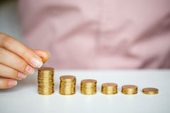 Female hand stacking gold coins into increasing columns Royalty Free Stock Photography