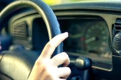 Female hand on steering wheel Stock Images