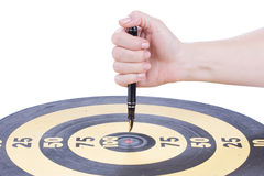 Female hand sticks a Fountain pen in the target center. Dartboard over white Stock Photography