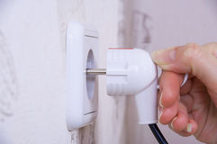 Female Hand Sticks A Plug In The Socket Royalty Free Stock Photo