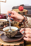 Female hand stirred and squeezed into a cup of tea herbal ingre Stock Images