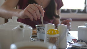 Female hand stirring sugar or milk in a cup of hot coffee or tea. Close up stock footage