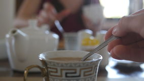 Female hand stirring sugar or milk in a cup of hot coffee or tea. Slow motion.  stock footage