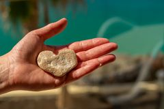 A female hand with a stone in the shape of a heart in front of a blurred background royalty free stock photos
