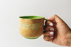 Female hand stretches a beautiful handmade cup with tea or coffee Royalty Free Stock Photo