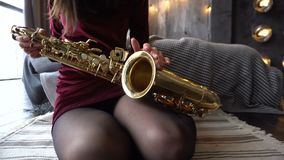 Female hand is stroking a saxophone. Saxophone lies on a woman`s lap stock video