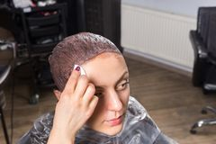 Female hand of stylist wiping off the remains of paint with a co. Tton disc from the head of women while she is sitting in hairdresser armchair in beauty salon Royalty Free Stock Photos