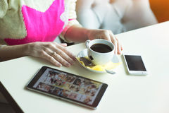 Female hand on the table, technology, internet, woman drinking coffee Stock Photo