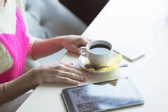 Female hand on the table, technology, internet, woman drinking coffee Royalty Free Stock Image