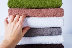 Female hand take stack bath towels colorful cotton Royalty Free Stock Photos