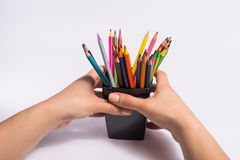 Female hand takes the box with color pencils on white background. Copy space for text. Royalty Free Stock Image