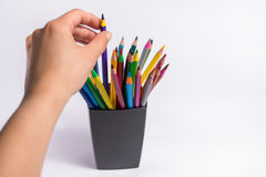 Female hand takes color pencil from the box on white background. Copy space for text. Royalty Free Stock Images