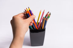 Female hand takes color pencils from the box on white background. Copy space for text. Royalty Free Stock Photos