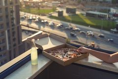 A female hand takes a huge piece of pizza on sunset and city background. Concept stock images