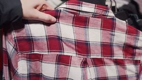 Female hand takes a plaid shirt from the hanger at the modern shop.