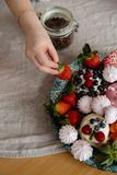 Female hand takes a strawberry. Beautiful and colorful mix of zephyr and fruits on a table in a kitchen stock photos