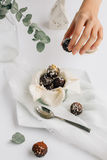 Female Hand taking Dark Chocolate and Coconut Truffle from Pot on White Table Stock Image