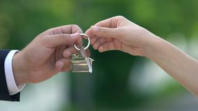 Female hand taking house key from real estate agent, apartment rent, property