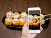 Female hand taking photo of maki sushi with mobile phone Royalty Free Stock Images