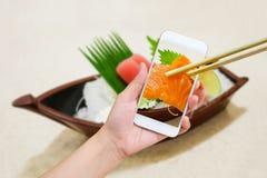 Female hand taking photo of sashimi sushi set Stock Photo