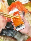 Female hand taking photo of sashimi sushi set Stock Image
