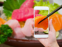 Female hand taking photo of sashimi sushi set Stock Photography