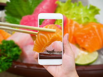 Female hand taking photo of sashimi sushi set Stock Images