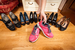 Female hand taking pink sneakers from wardrobe. Closeup photo of female hand taking pink sneakers from wardrobe Royalty Free Stock Image