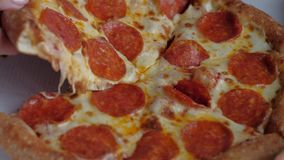 Female hand taking slice of pepperoni pizza from delivery box. Junk food stock footage