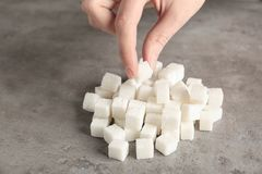 Female hand taking sugar cube. From table Royalty Free Stock Photo