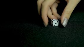 Female hand throwing dice on black background in slow motion. Two standard six-sided pipped dice with rounded corners on. Black background 4K Royalty Free Stock Image